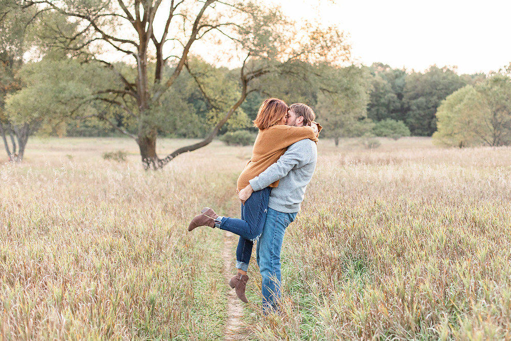 Engagement Photos Al Sabo Land Preserve Kalamazoo Michigan Open Field cute couple kissing guy lifting girl