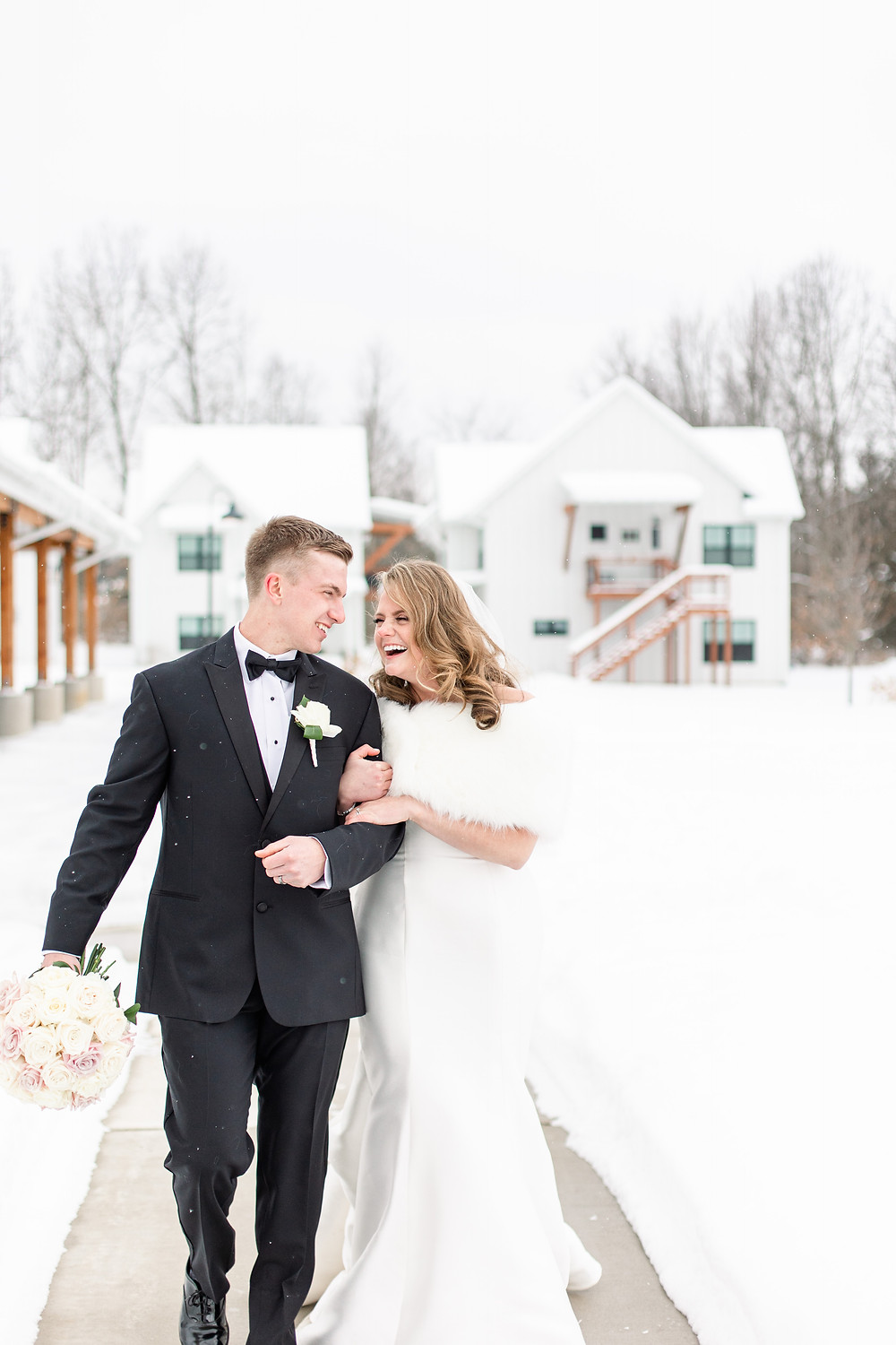 Josh and Andrea wedding photography husband and wife photographer team michigan venue Bay Pointe Woods shelbyville snow winter wedding bride and groom smiling laughing walking
