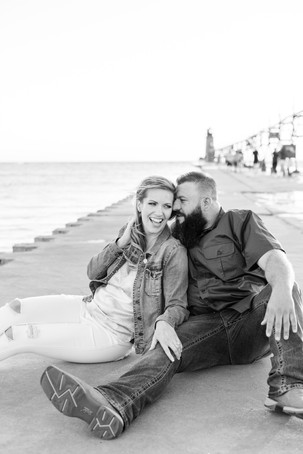 Engagement Photos Engaged Couple South Haven Beach Lighthouse Pier Michigan Engaged Couple sitting on pier snuggling laughing
