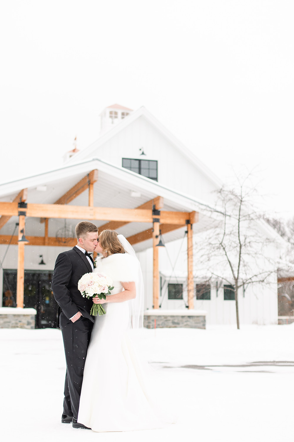 Josh and Andrea wedding photography husband and wife photographer team michigan venue Bay Pointe Woods shelbyville snow winter wedding bride and groom kissing