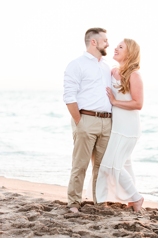 white dress engagement photos cute couple standing smiling on city beach new buffalo michigan