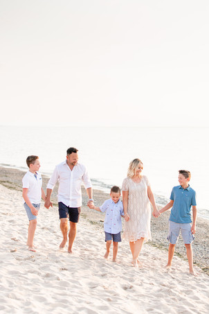Family of 5 walking holding hands on beach sand Lake Michigan