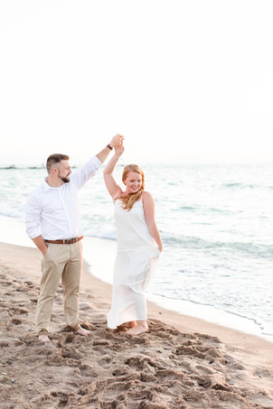 white dress engagement photos cute couple twirling on city beach new buffalo michigan