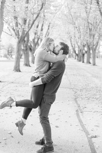 man and woman standing on a road with trees and fall colors kissing