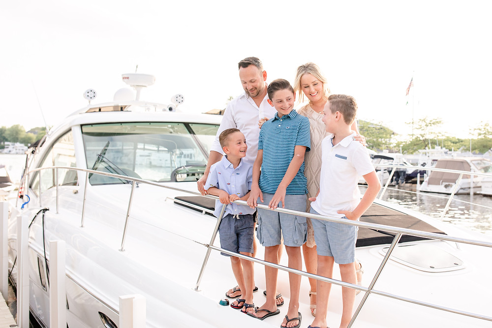 family of 5 photos standing and laughing on bow of yacht boat new buffalo michigan
