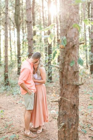 Engagement Photos Al Sabo Land Preserve Kalamazoo Michigan cute couple kissing in Tall row of Pines