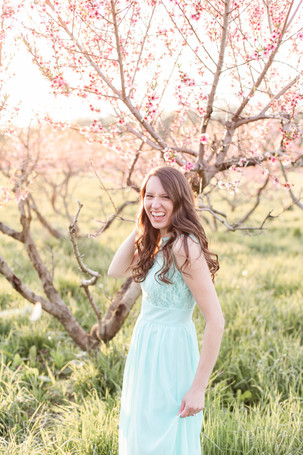 pretty woman in field at sunset laughing