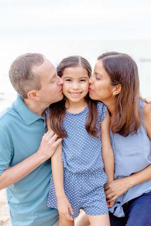 dad and mom kissing young girl beach Lake Michigan South Haven Michigan