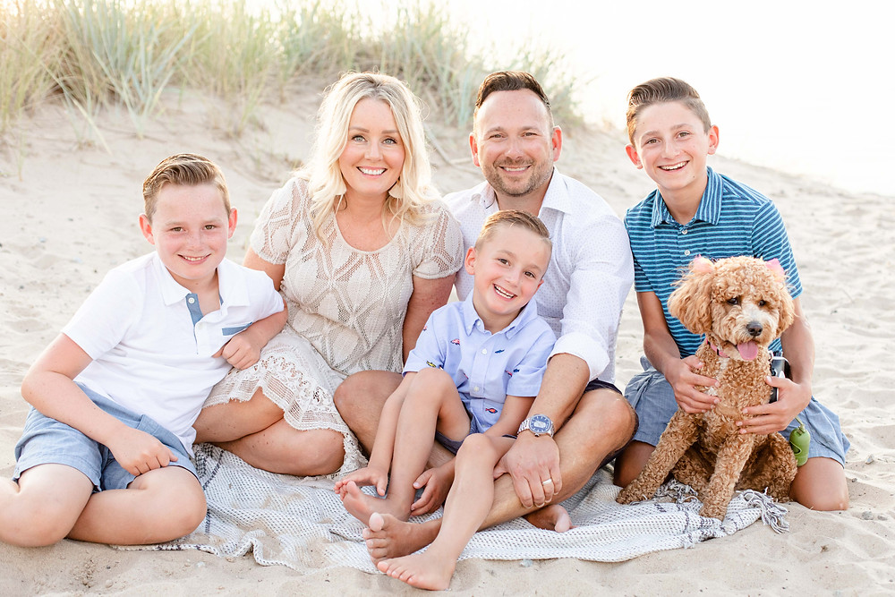 Family photos sitting in the beach sand with dog dune grass New Buffalo Michigan