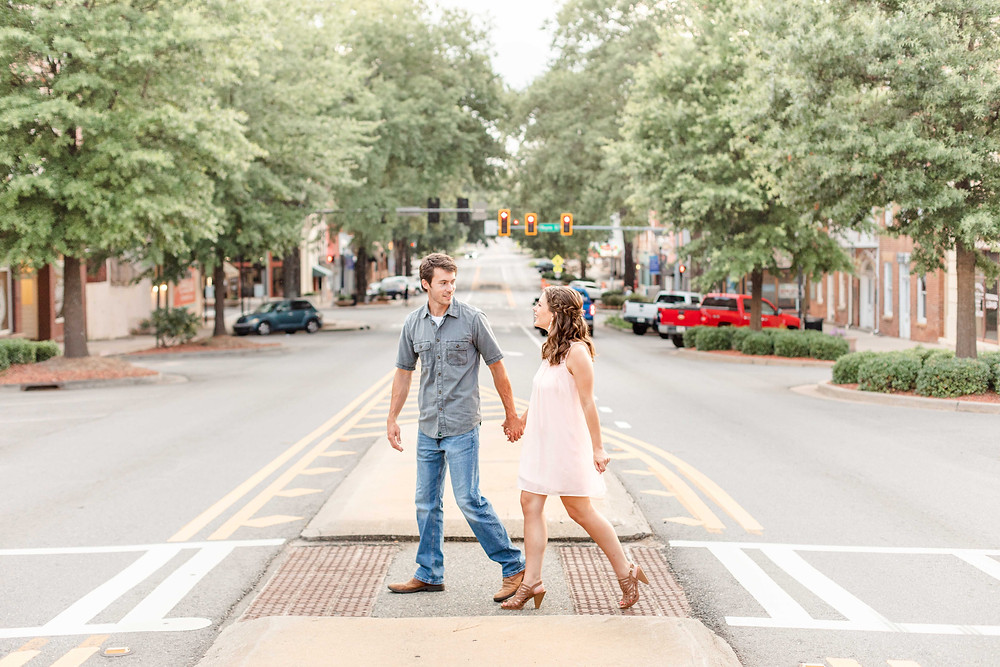 engagement photos cute couple walking crosswalk downtown Milledgeville Georgia