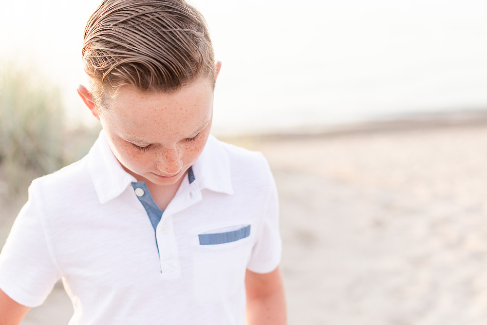young boy looking down beach photos dune grass Lake Michigan