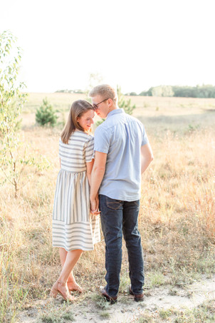 Engagement Photos Riley Trails Holland Michigan Engaged Couple snuggling open field