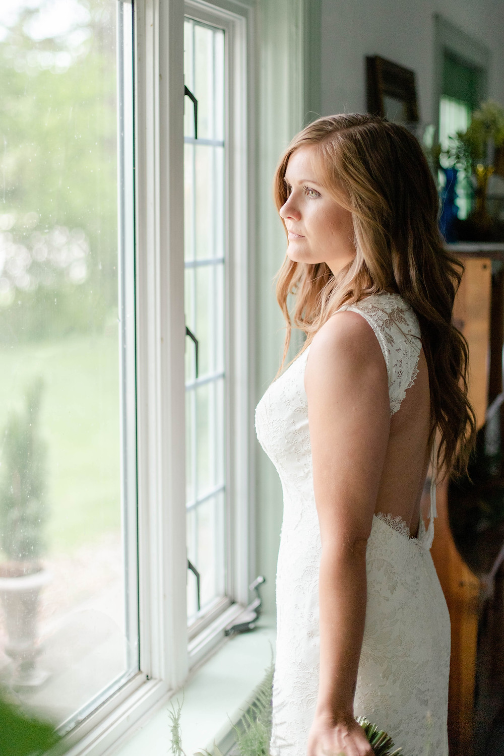 bride looking out window indoor ceremony in the details byron center truer design