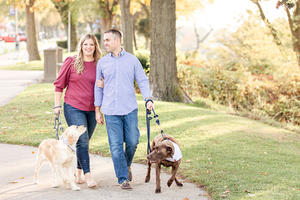 Engagement Photos Downtown Saint Joseph MI cute couple walking with two dogs