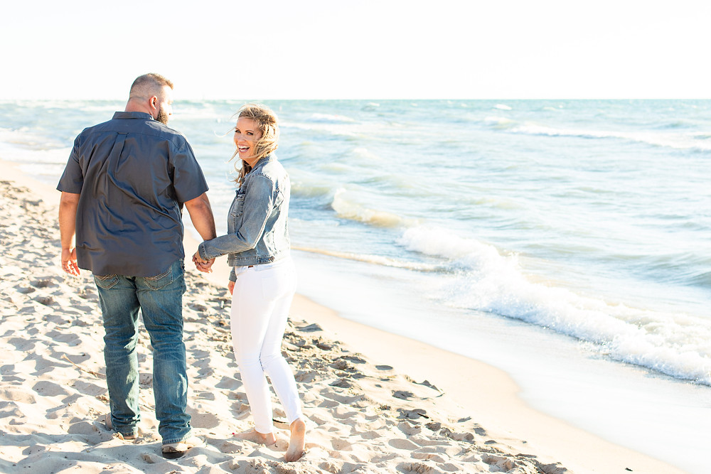Engagement Photos South Haven Beach Michigan Engaged Couple walking laughing on beach