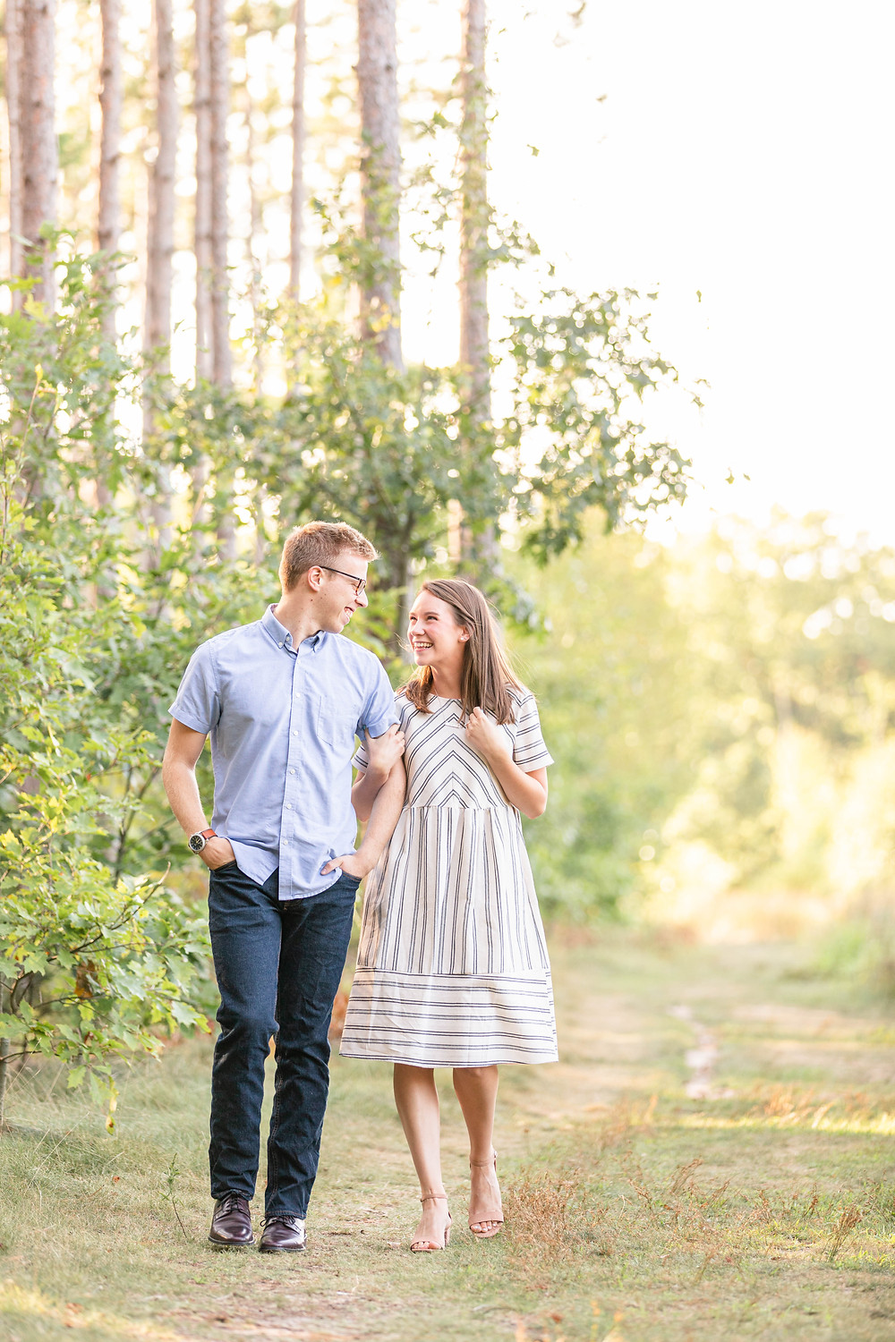 Engagement Photos Riley Trails Holland Michigan Engaged Couple holding arms walking smiling