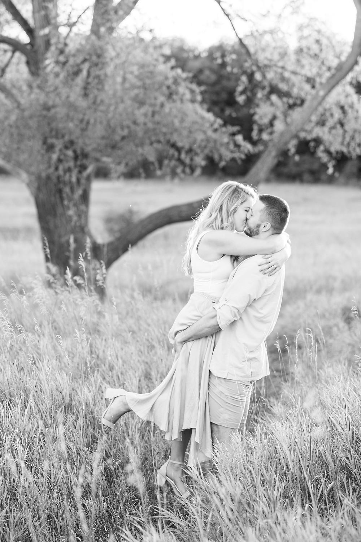 Engagement Photos Al Sabo Land Preserve Kalamazoo Michigan Open Field guy lifting girl and kissing
