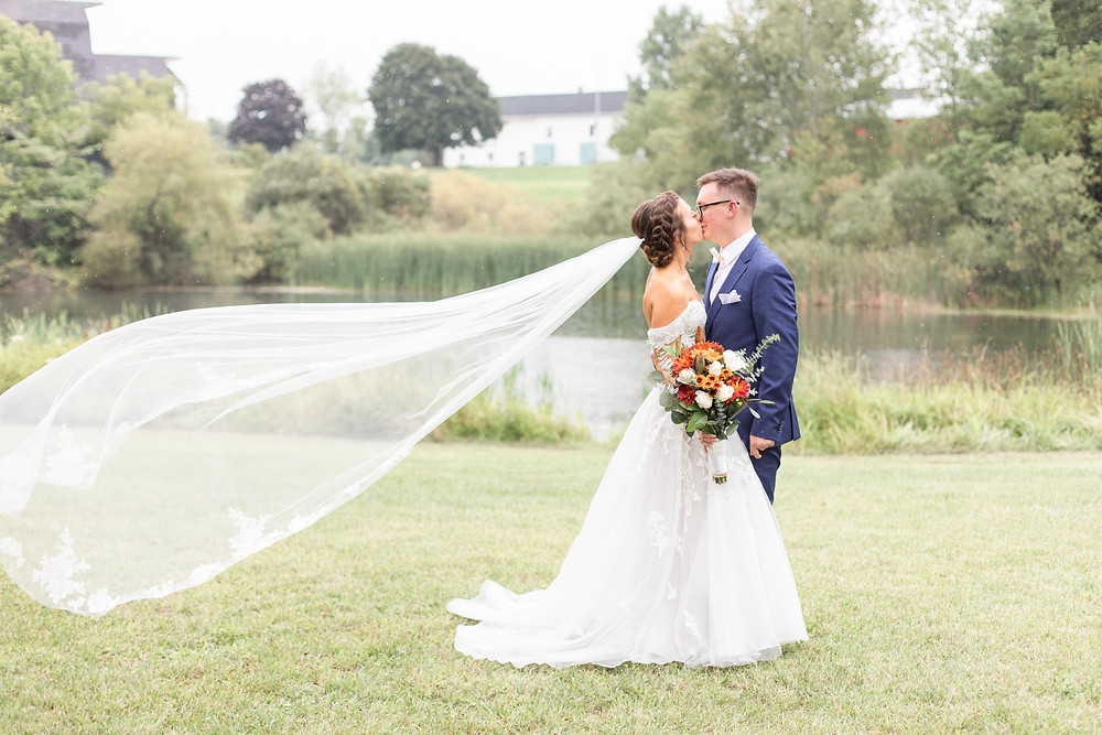 Bride and Groom kissing veil Bridal bouquet fall colors Saint Patricks Park South Bend Indiana