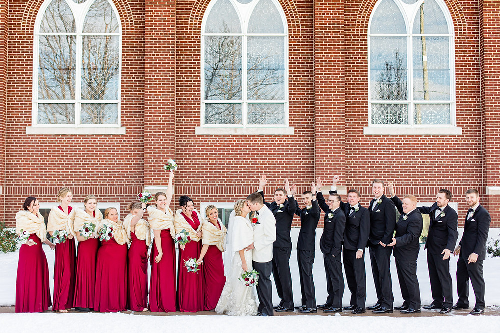 josh and Andrea photography husband and wife team michigan winter wedding south haven st basils bride and groom kissing bridal party