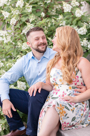 engagement photos couple sitting near flower bush journeyman distillery weddings three oaks michigan