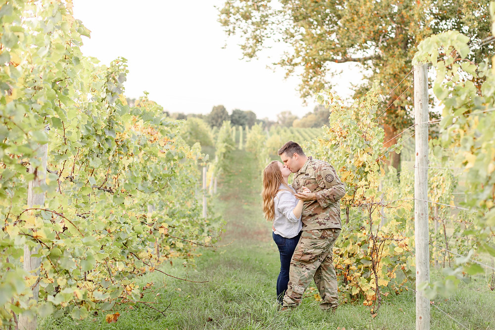 Engagement photos cute couple kissing Round Barn Winery Baroda Michigan army uniform vineyard