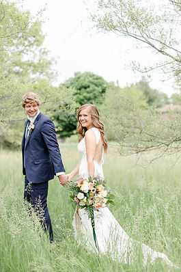 Josh and Andrea Photography husband and wife team michigan bride and groom Grand Rapids wedding smiling walking holding hands