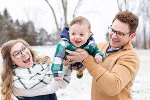 cute family standing smiling in snow