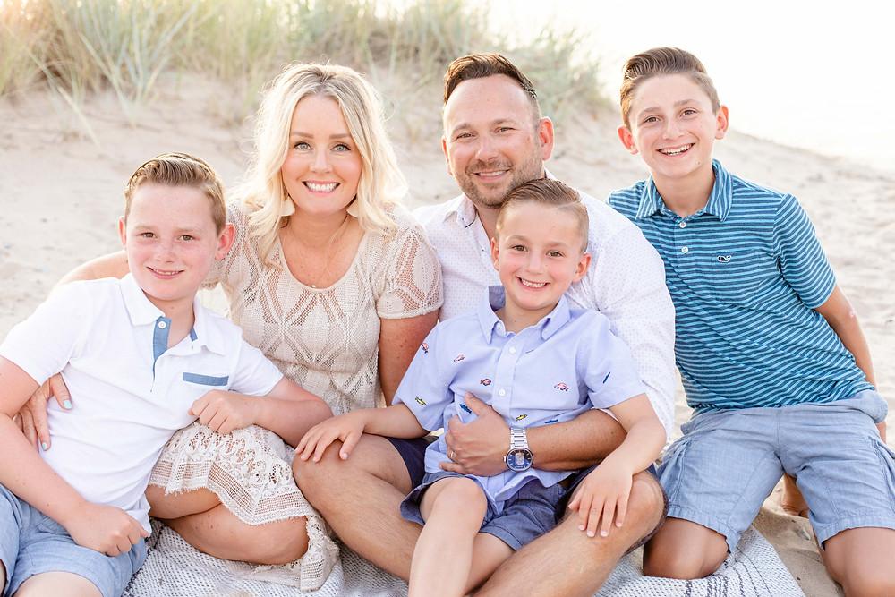 family of 5 photos sitting in beach sand dune grass Lake Michigan