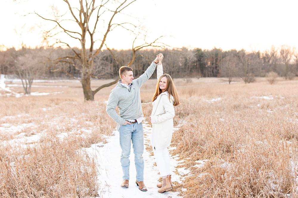 Josh and Andrea wedding photography husband and wife team michigan engagement session Al sabo land preserve couple laughing dancing in snowy field