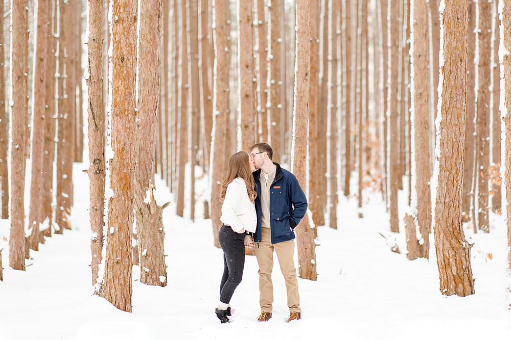 Josh and Andrea wedding photography husband and wife team michigan Grand Haven Rosy Mound engagement session fiance snowy forest woods kissing standing