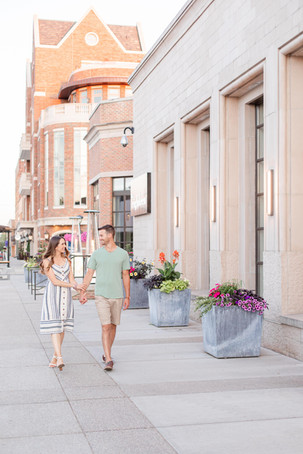 engaged couple walking holding hands downtown Midland Michigan
