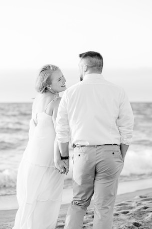 white dress engagement photos cute couple holding hands smiling on city beach new buffalo michigan