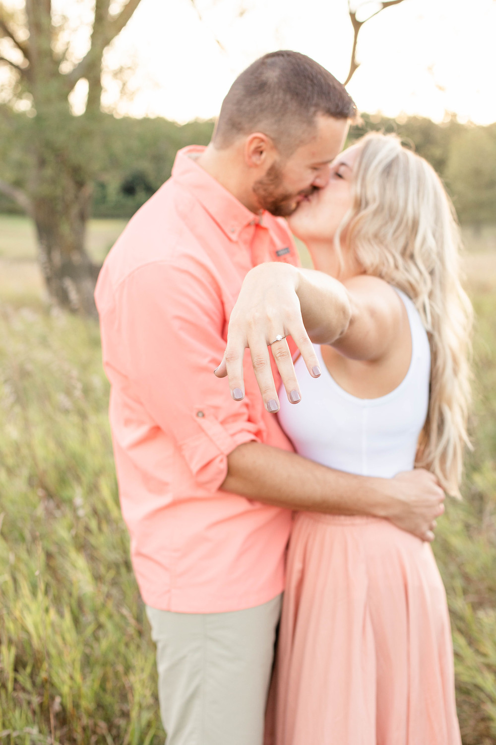 Engagement Photos Al Sabo Land Preserve Kalamazoo Michigan Open Field cute couple smiling at eachother holding out engagement ring hand