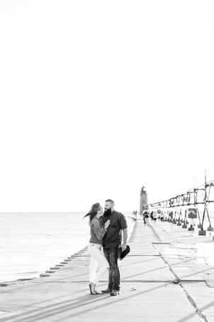 Engagement Photos Engaged Couple South Haven Beach Lighthouse Pier Michigan Engaged Couple standing on pier