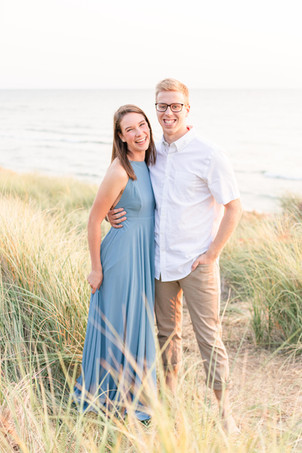 Engagement Photos Tunnel Park Beach Holland Michigan Engaged Couple smiling at camera standing in dune grass
