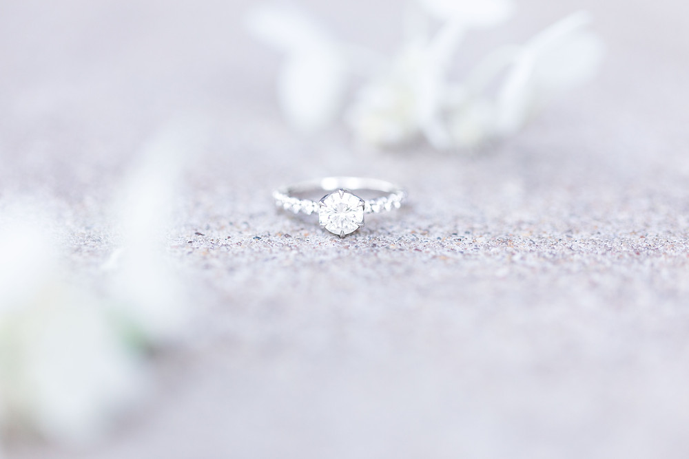 engagement ring on stone step with white flowers