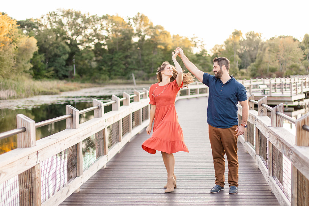 Cute couple smiling dancing on bridge provin trails engagement session