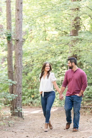 Cute couple smiling walking provin trails Grand Rapids engagement session