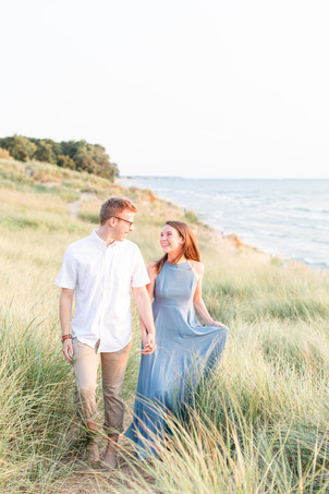 Engagement Photos Tunnel Park Beach Holland Michigan Engaged Couple smiling walking on bluff in dune grass