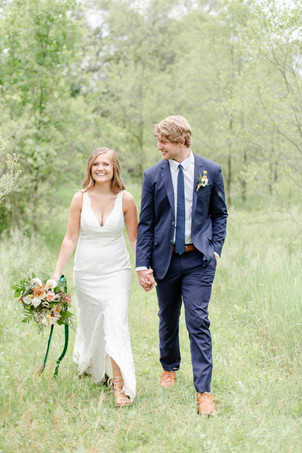 bride and groom walking smiling in field in the details byron center truer design