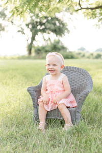 cute child girl sitting on chair in grass