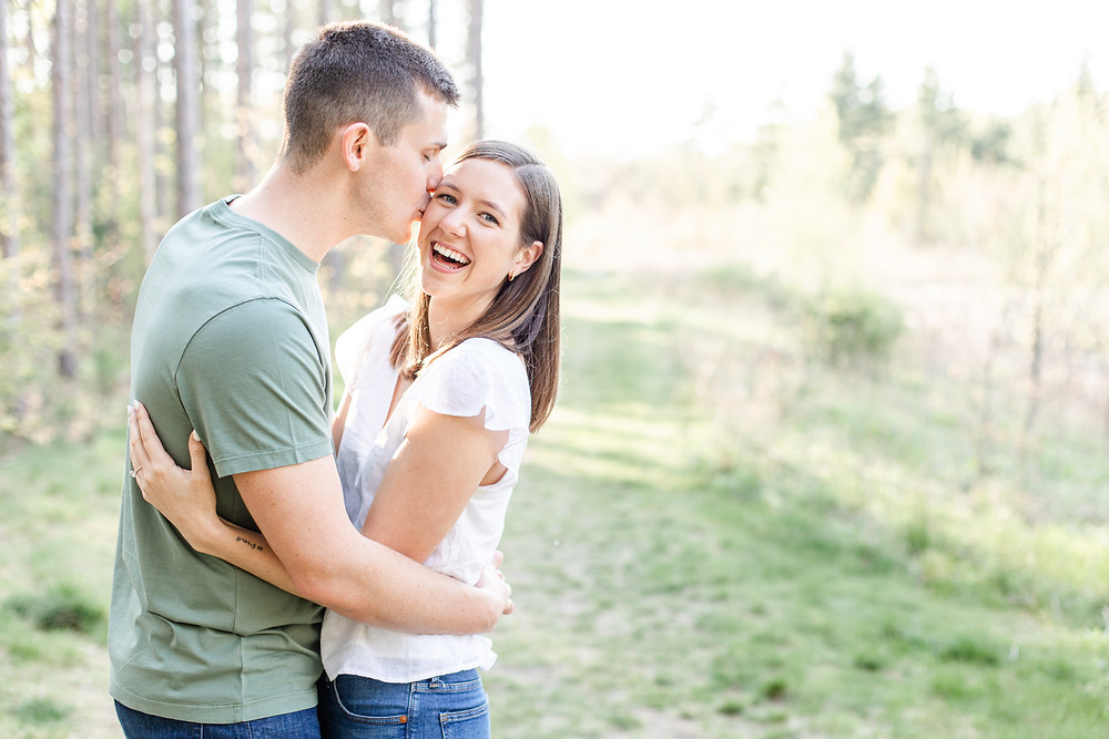 Josh and Andrea wedding photography husband and wife photographer team michigan engagement pictures session photo shoot fiance Riley Trails kissing laughing