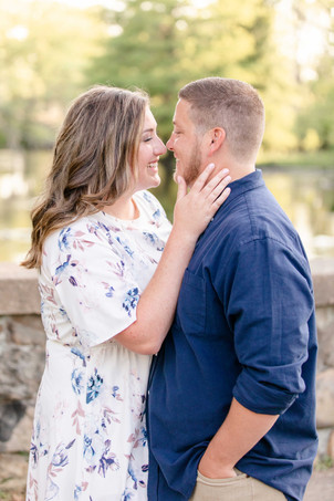 engagement photos cute couple kissing on stone bridge at milham park kalamazoo michigan