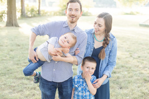 cute family standing smiling on grass