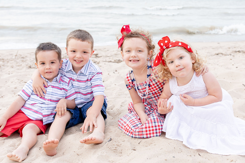 South Haven Family shoot small children cousins smiling on the beach at Lake Michigan red white and blue outfits