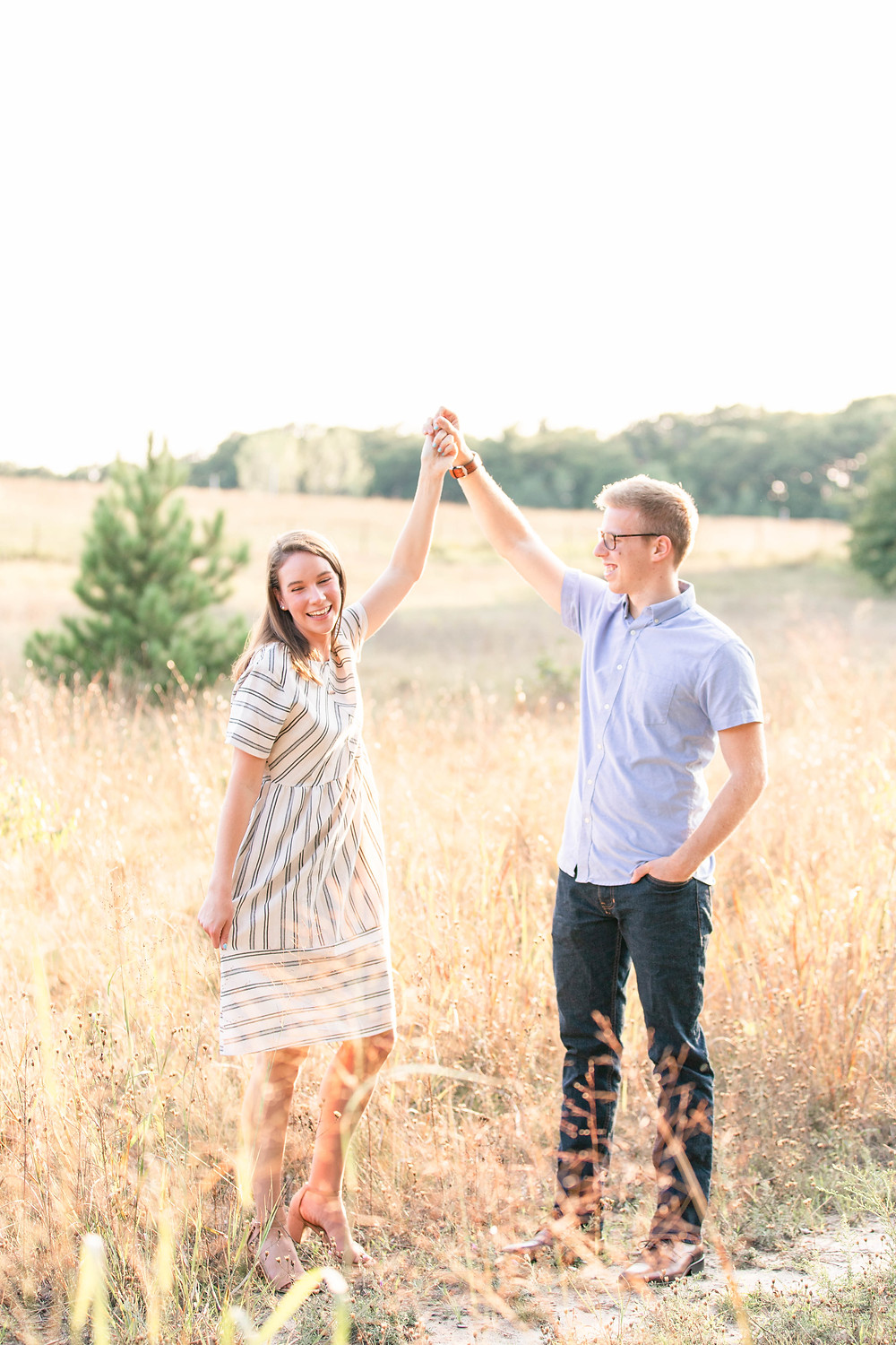 Engagement Photos Riley Trails Holland Michigan Engaged Couple twirling in open field smiling