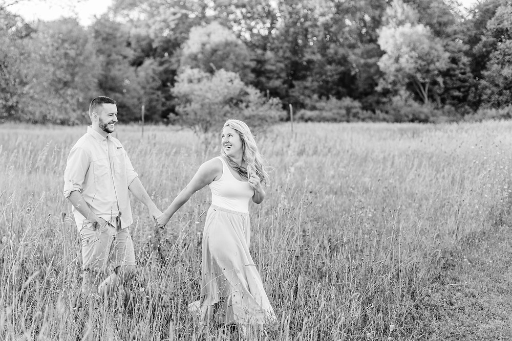 Engagement Photos Al Sabo Land Preserve Kalamazoo Michigan Open Field couple walking holding hands