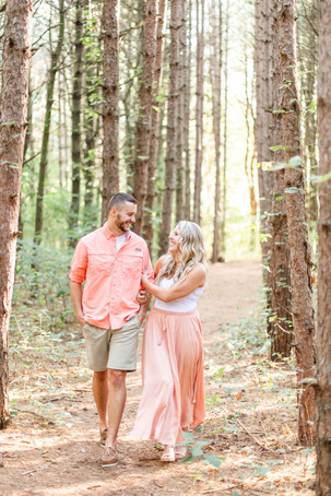 Engagement Photos Al Sabo Land Preserve Kalamazoo Michigan cute couple walking holding arms in Tall row of Pines