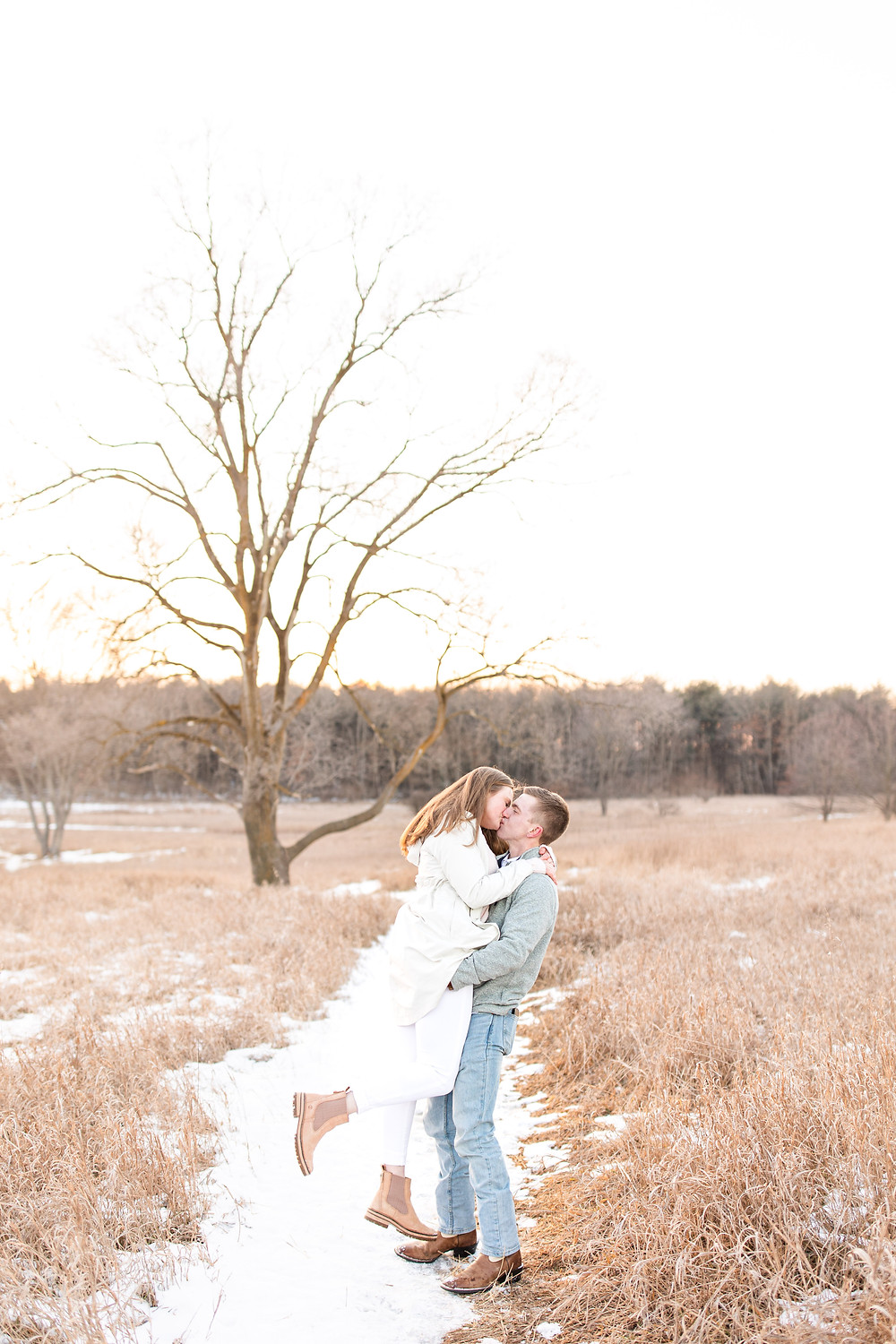 Josh and Andrea wedding photography husband and wife team michigan engagement session Al sabo land preserve couple lifting kissing in snowy field