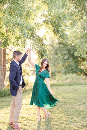 engaged cute couple twirling at trees near The Tridge Midland Michigan
